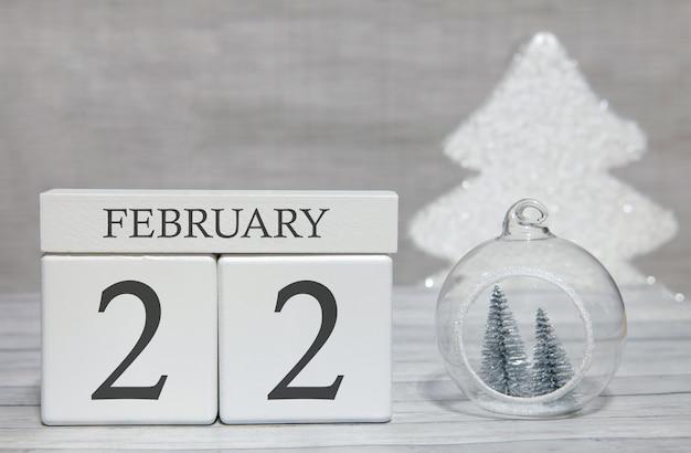Würfelformkalender für den 22. februar auf holzoberfläche und hellem hintergrund
