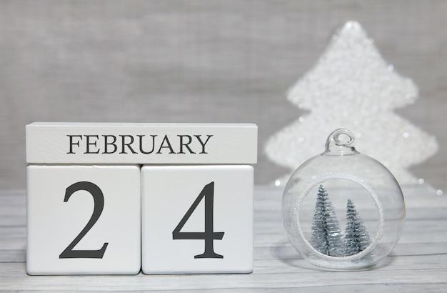 Würfelformkalender für den 24. februar auf holzoberfläche und hellem hintergrund