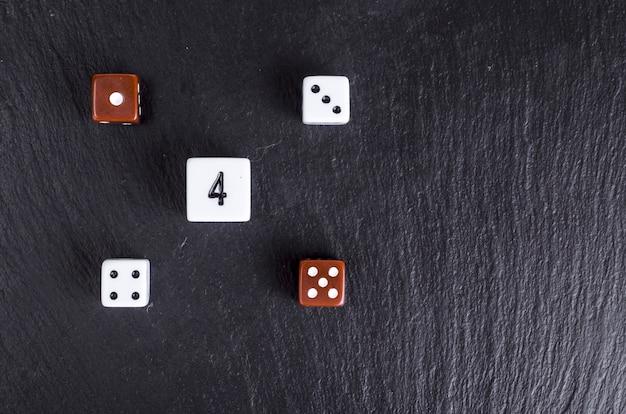 Würfeln mit einer beliebigen zahl über schwarz. casino-glücksspiel-konzept.