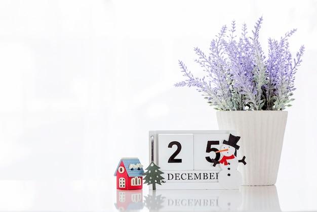 Würfeln sie den hölzernen kalender, der datum am 25. dezember mit holzhaus, houseplant und schneemann zeigt