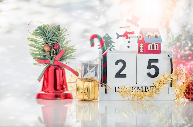 Würfeln sie den hölzernen kalender, der datum am 25. dezember mit kleinem holzhaus, weihnachtsbaum zeigt
