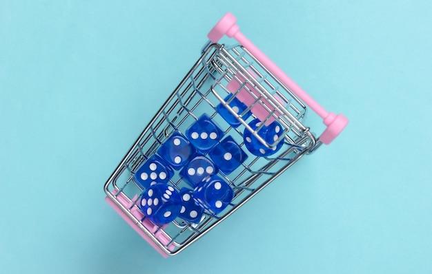 Würfeln sie in einem mini-supermarktwagen auf einer blauen oberfläche