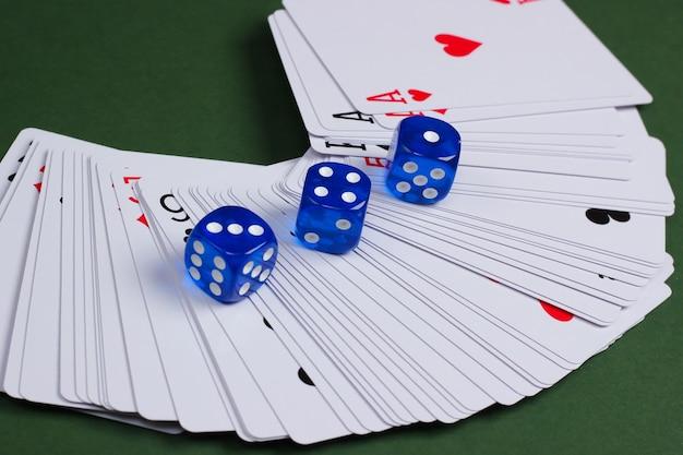 Würfeln sie mit spielkarten auf einer grünen fläche. spielsucht, poker, casino