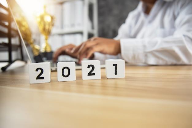 Würfelnummer von 2021 auf holztisch mit geschäftsmann, der am laptop zum erfolg arbeitet und mit trophäe oder auszeichnung auf tischhintergrund gewinnt