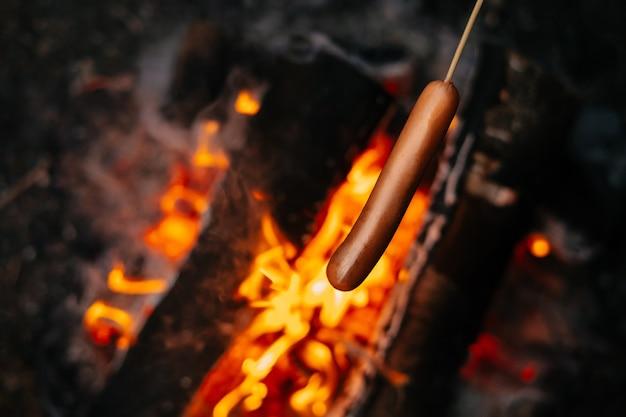 Würstchen am lagerfeuer am abend auf einem holzstab kochen konzept der erholung im freien