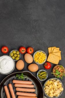 Würstchen in der pfanne. speckkäse, gemüse, kekse müsli joghurt: zutaten für das kontinentale frühstück