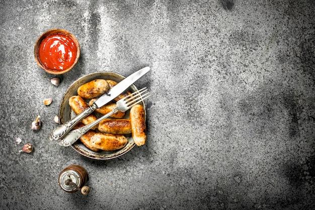 Würstchen in einer pfanne mit tomatensauce auf einem rustikalen hintergrund
