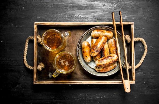 Würstchen mit bier auf einem holztablett. auf der schwarzen tafel.