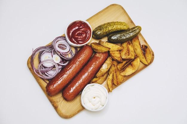 Würstchen mit bratkartoffeln, saucen, zwiebeln und eingelegten gurken auf holzbrett auf weißem hintergrund draufsicht