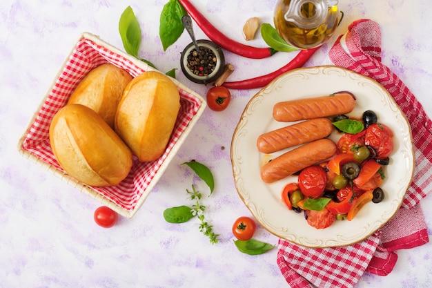 Würstchen mit gemüse nach griechischer art auf teller gegrillt.