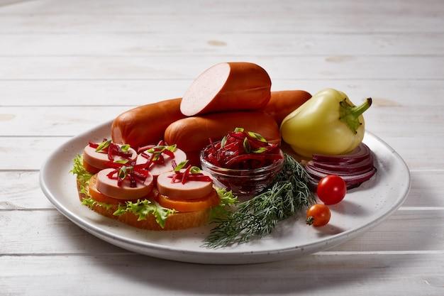 Würstchen mit gemüse und kräutern garnieren mit saucen und brot auf einem grauen keramikteller auf einem weißen holztisch.