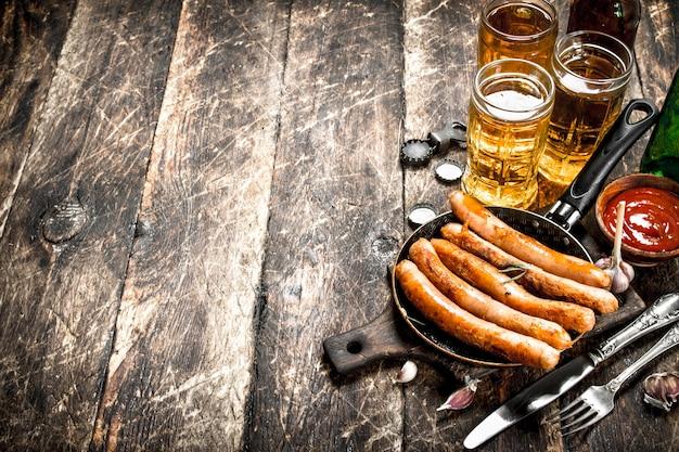 Würstchen mit kaltem bier und soße auf einem hölzernen hintergrund