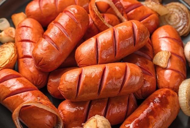Würstchen mit zwiebeln und knoblauch nahaufnahme. seitenansicht, horizontal. fastfood.
