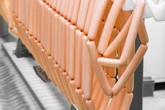 Würstchen-produktionslinie, würstchen hängen in einer reihe