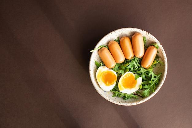 Würstchen salat pochiertes ei blätter grüne blütenblätter salatmischung frisch gesund
