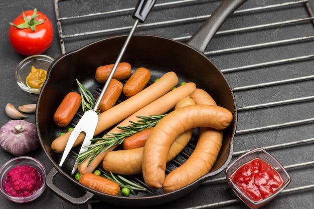 Würstchen und rosmarinzweige in der pfanne auf metallrost. tomatenmark und tomaten, senf und knoblauch auf dem tisch. schwarzer hintergrund. draufsicht