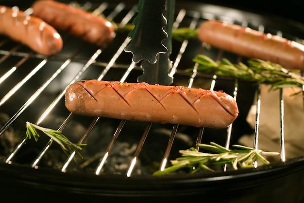 Würste auf heißem grill mit rauche
