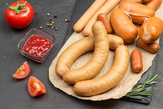 Würste verschiedener sorten auf papier. tomatenmark und tomate auf dem tisch. schwarzer hintergrund. draufsicht