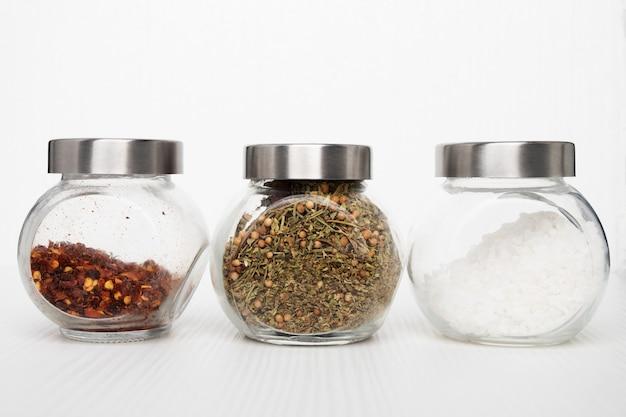 Würzen in gläsern auf weißem hintergrund. meersalz, kräutermischung, scharfer chili