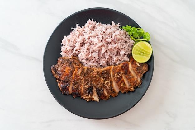 Würzig gegrilltes jamaikanisches jerk chicken mit reis - jamaican food style Premium Fotos