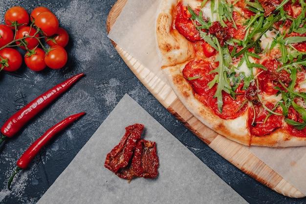 Würzige appetitliche neapolitanische pizza an bord mit kirschtomaten und chili, freier platz für text