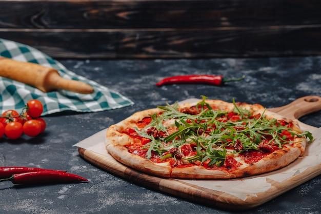 Würzige appetitliche neapolitanische pizza an bord mit kirschtomaten und chili