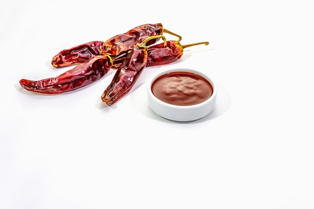 Würzige chili-sauce in einer schüssel mit scharfen chilischoten