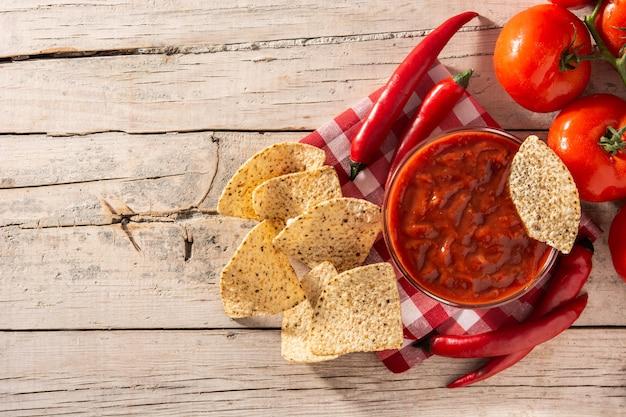 Würzige chilisauce in der schüssel mit nacho-chips auf holztisch