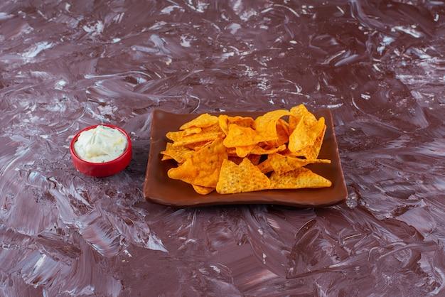 Würzige chips auf einem teller neben einer schüssel mayonnaise auf dem marmortisch.