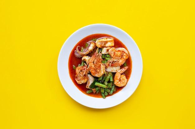 Würzige gebratene meeresfrüchte und lange bohnen mit roter curry-paste. thai essen