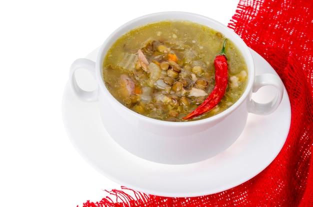 Würzige grüne linsen-chili-suppe auf weißem teller