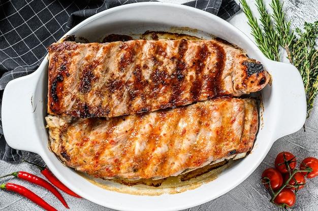 Würzige, heiß gegrillte schweinerippchen vom grill, serviert in einer pfanne. grauer hintergrund. draufsicht.
