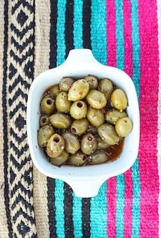 Würzige in essig eingelegte oliven in einer weißen schüssel an einem strandpicknick