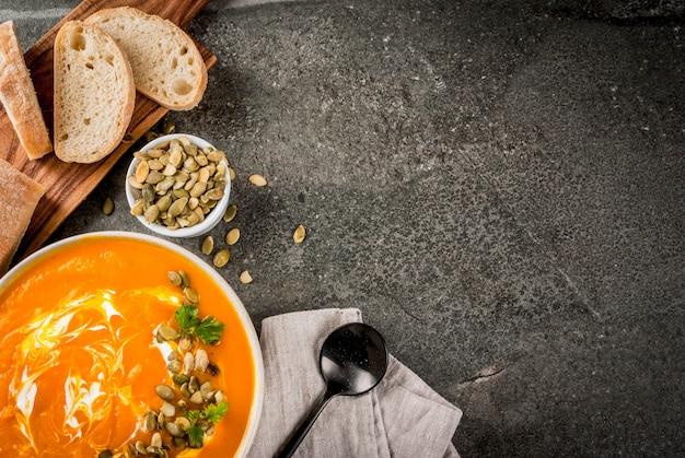 Würzige kürbissuppe mit kürbiskernen, sahne und frisch gebackenem baguette auf schwarzem steintisch