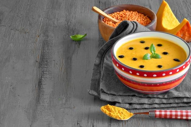 Würzige kürbissuppe mit roten linsen und kurkuma, serviert mit minzblättern und tropfen balsamico vinega