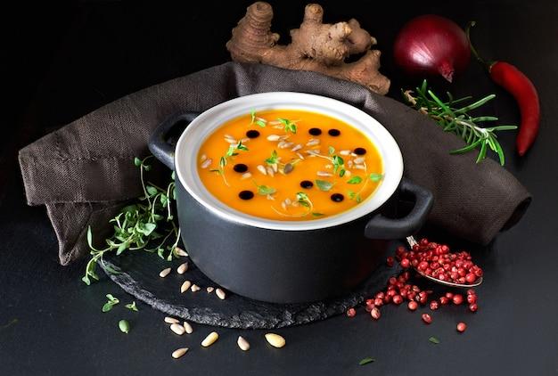 Würzige kürbissuppe serviert in keramikpfanne mit kürbisöl und sonnenblumenkernen