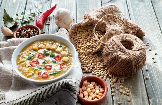 Würzige linsensuppe mit paprika, knoblauch und zwiebel auf rustikalem holztisch.