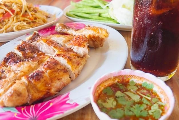 Würzige mahlzeit nach thailändischer art, hähnchen vom grill mit würzigem papayasalat und kaltes getränk
