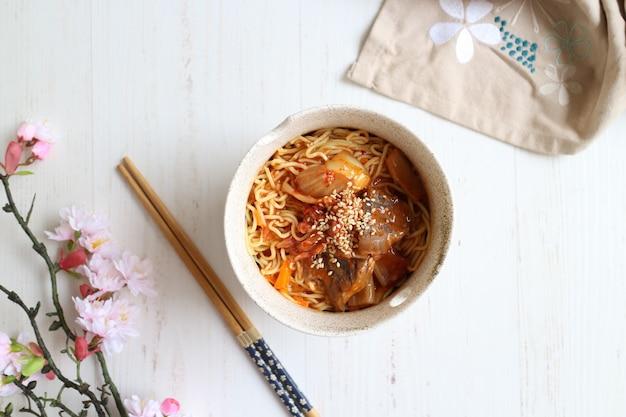 Würzige ramen-nudeln mit pilz und kimchi auf der schüssel mit stäbchen
