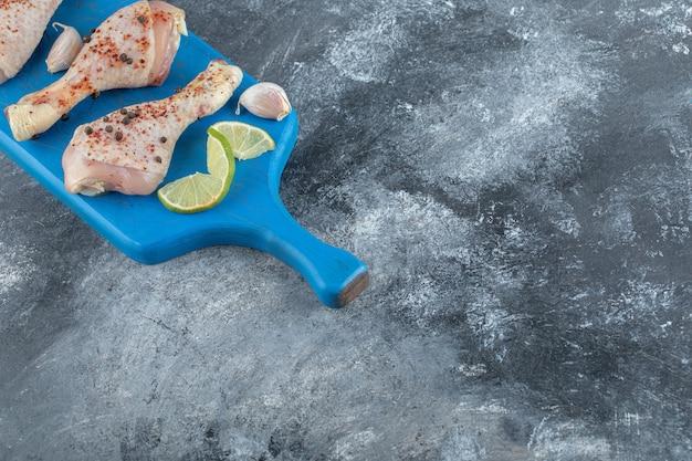 Würzige rohe hähnchenschenkel über blauem holzbrett. draufsicht.