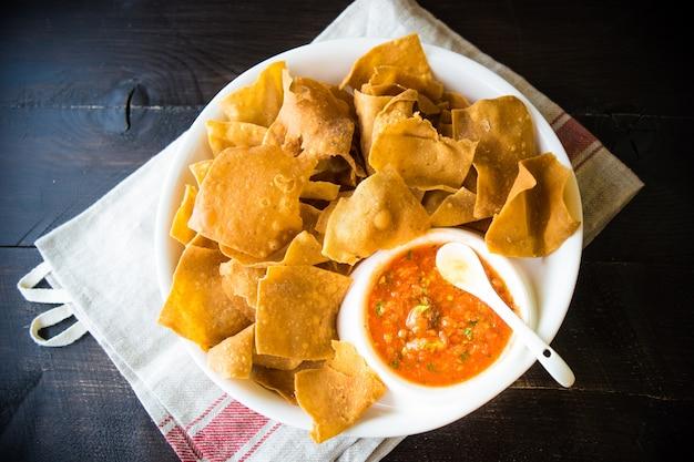 Würzige rote salsa mit einer platte von tortillachips