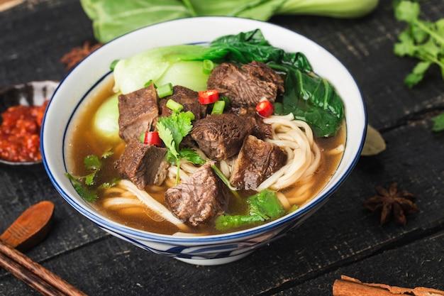 Würzige rote suppe rindfleischnudel in einer schüssel auf holztisch