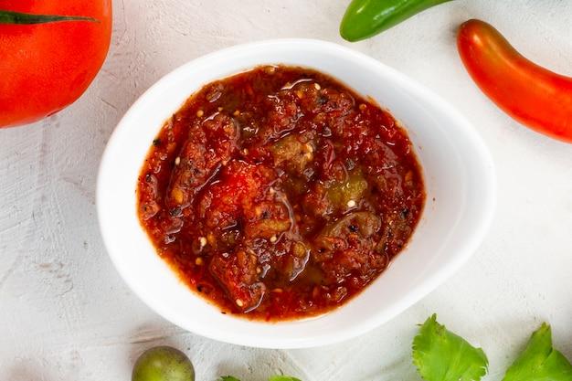 Würzige salsa der nahaufnahme mit weißem hintergrund