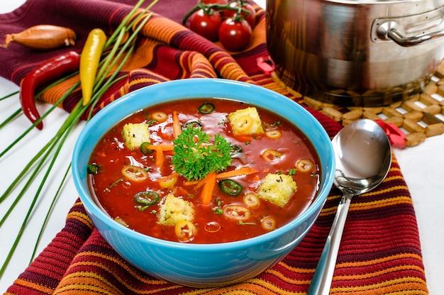 Würzige scharfe chili-tomatensuppe mit brotwürfeln in einer schüssel