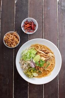 Würzige spaghetti mit thailändischen reisnudeln mit würziger hühnersauce auf holztisch.