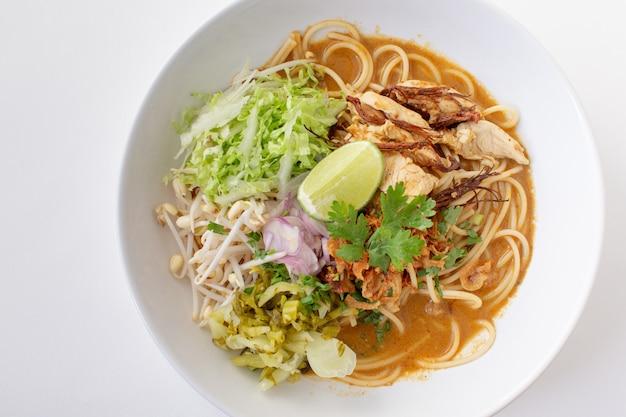 Würzige spaghetti mit thailändischen reisnudeln mit würziger hühnersauce isoliert weiß