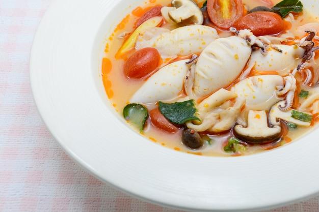 Würzige suppe aus tintenfischen und zitronengras mit pilzen, tomaten und kräutern