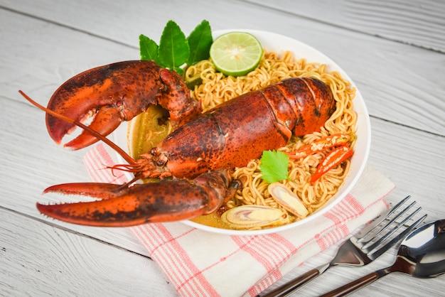Würzige suppe des nudelschüssel-hummers / gekochte meeresfrüchte mit suppenhummer-abendtische der sofortigen nudel und gewürzbestandteilen auf thailändischem lebensmittel der tabelle