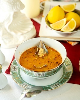 Würzige suppe mit austern und zitronenscheiben