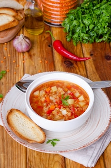 Würzige suppe mit roten linsen, tomaten, lauch, paprika, karotten und kartoffeln.